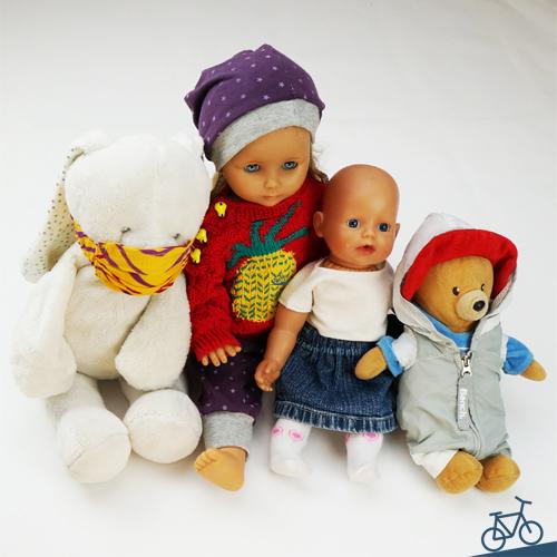 Hier siehst du einen Stoffhasen, zwei Puppen und einen Teddybären mit upgecycelter Kleidung.
