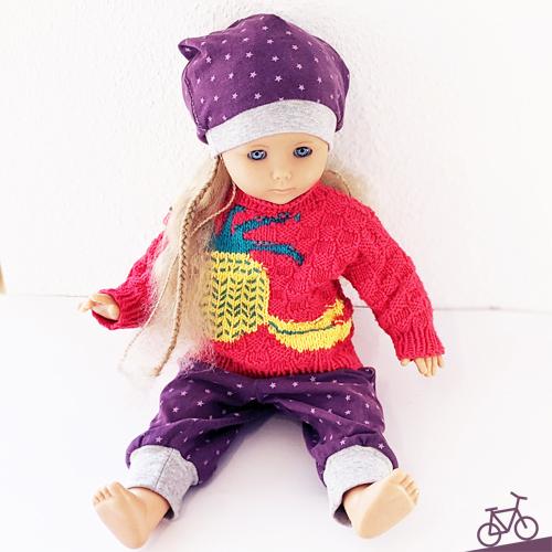 Hier siehst du unsere Puppe, die das neue Outfit aus Puppenhose und Puppenmütze trägt.