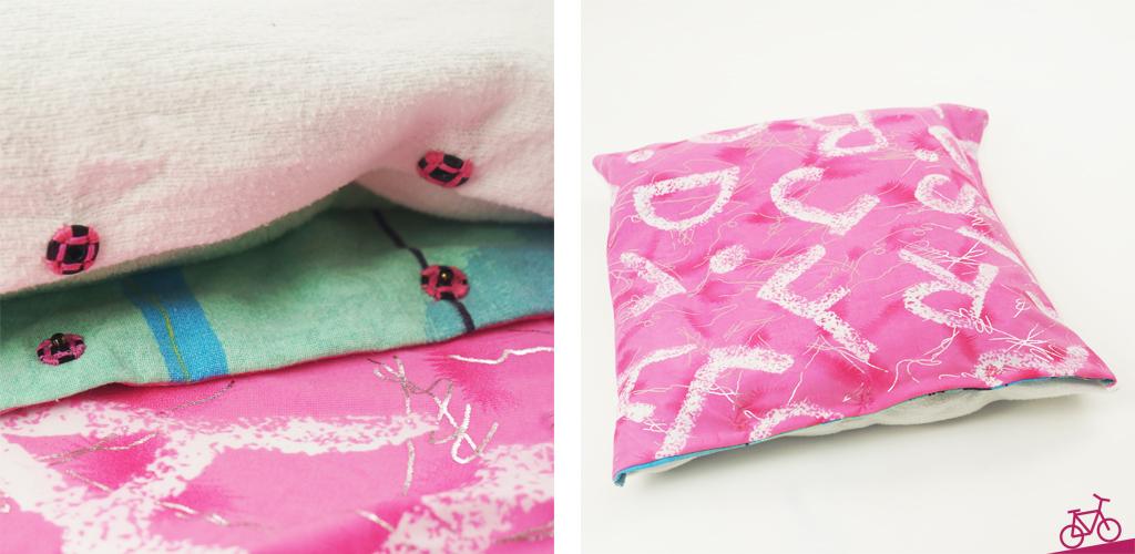 Angenähte Druckknöpfe und die Rückseite des Kissenbezugs aus einem pink-gemusterten Stoff