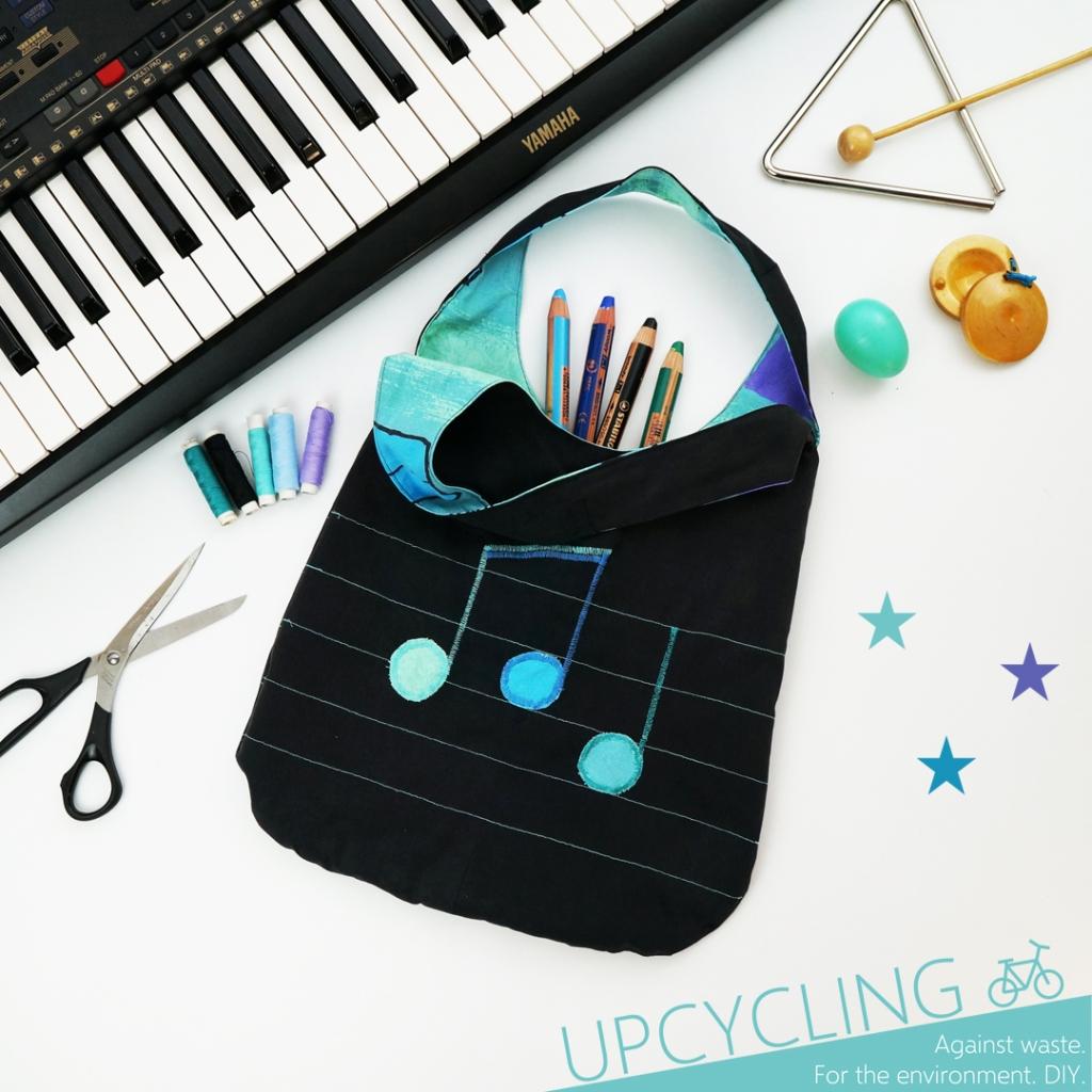 Hier siehst du eine musikalische schwarze Tasche mit türkisfarbenem Innenstoff und aufgestickten Noten.