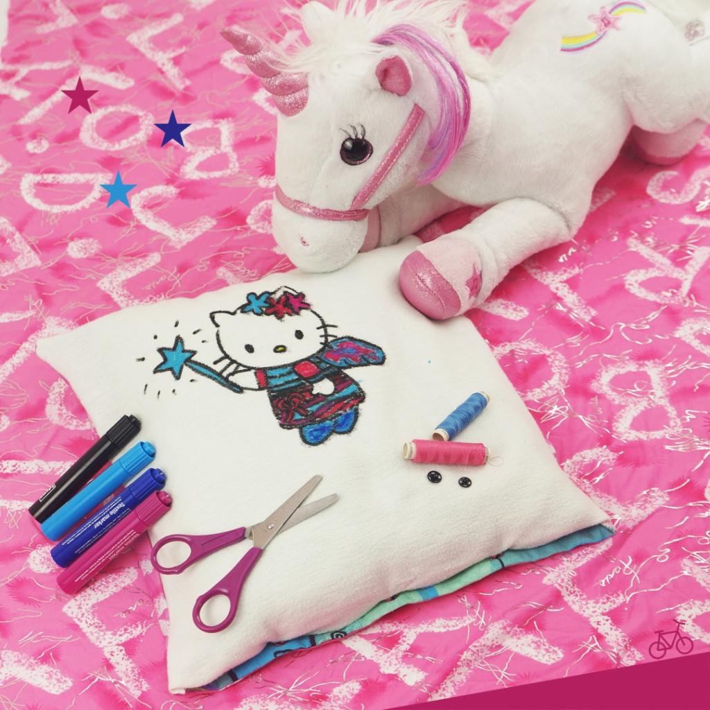 Bild von einem Kissen mit Hello Kitty als Fee, Stoffstiften, einer Schere und einem Kuscheltier-Einhorn