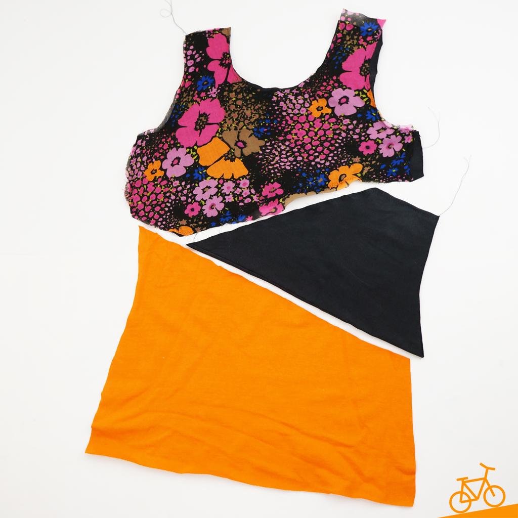 Drei Stoffstücke: oberer Teil mit Blumenmuster, Mittelteil in schwarz und unterer Teil in orange.