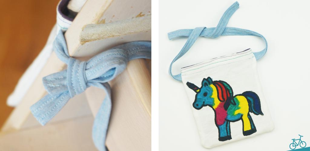 Kleine Tasche mit selbst gemaltem Einhorn, die mit Bändern an einem Kinder-Hochstuhl festgebunden werden kann