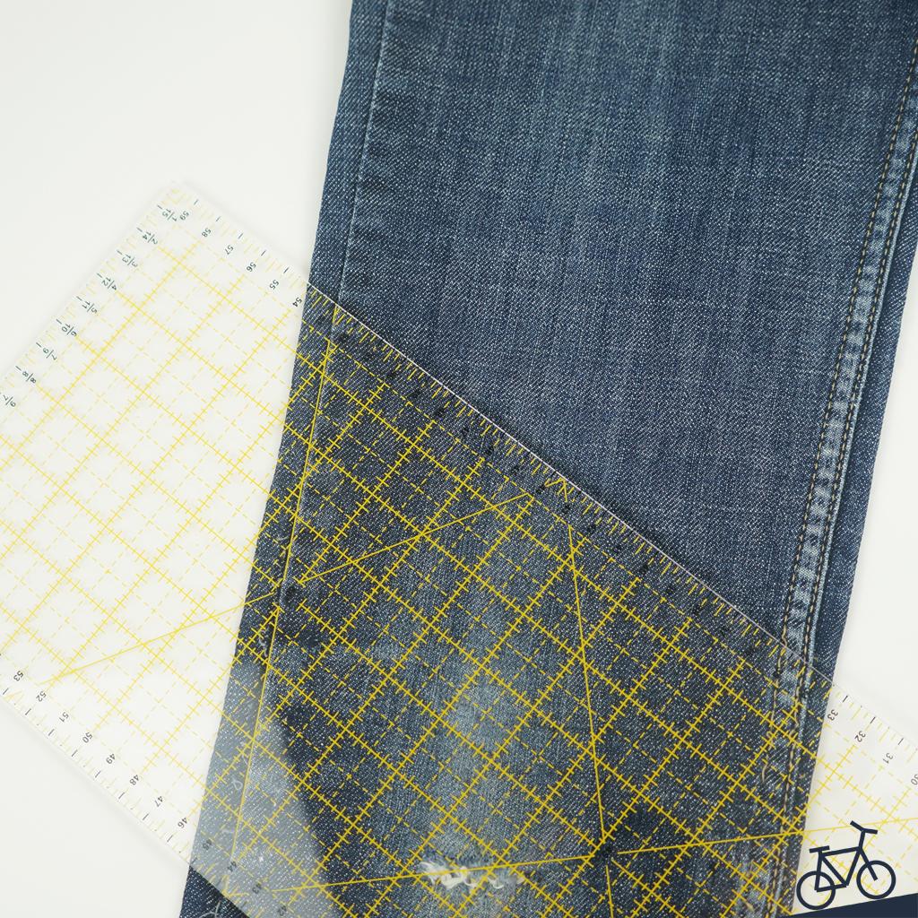 Mit dem Schneiderlineal Linien auf einer Jeans vorzeichnen