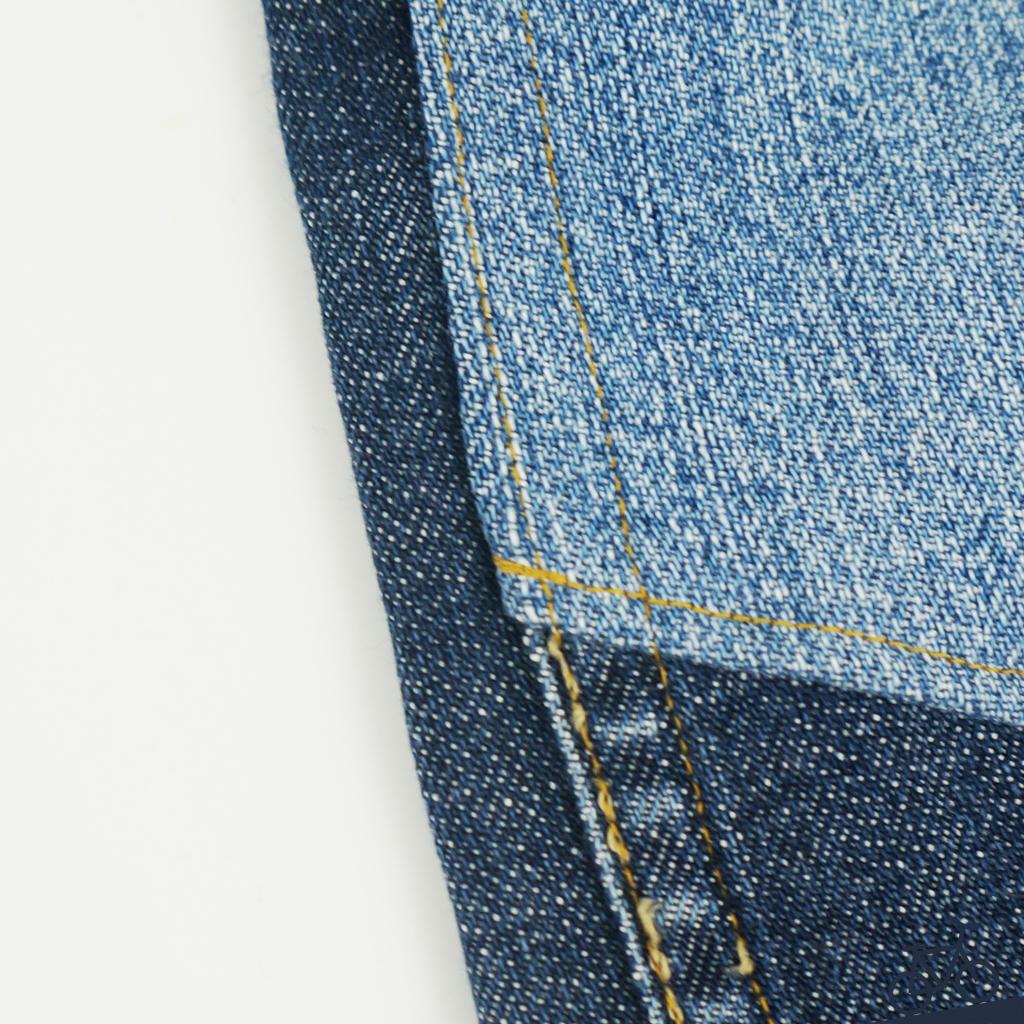 Goldene Nähte an einer blauen Jeans